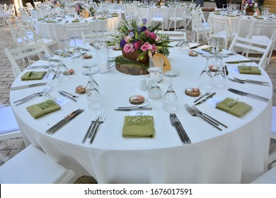 White color wedding table decorated with decorative and elegant for wedding. There are flowers, candles and serving plates on the wedding table.