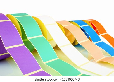 White and colored label rolls isolated on white background with shadow reflection. Color reels of labels for printers. Labels for direct thermal or thermal transfer printing. Close shot of stickers.