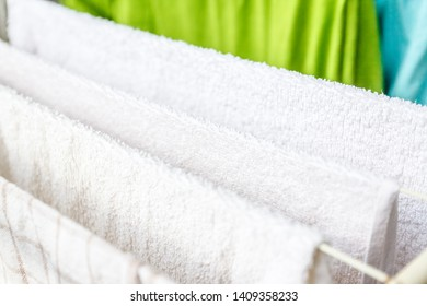 White and colored linen and towels to be dried on the clothesline.