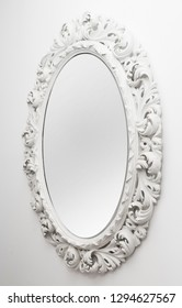 White colored vintage carved mirror on the wall
