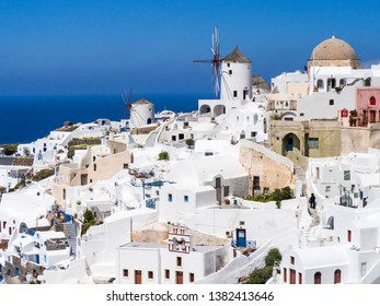 White and colorful buildings with windmill on the blue sky and blue water background in Oia, Santorini, Greece, beautiful view