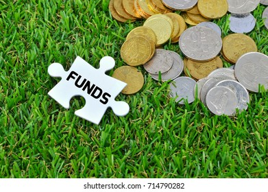 White colour missing jigsaw puzzle and coins with FUNDS word on the artificial grass background.