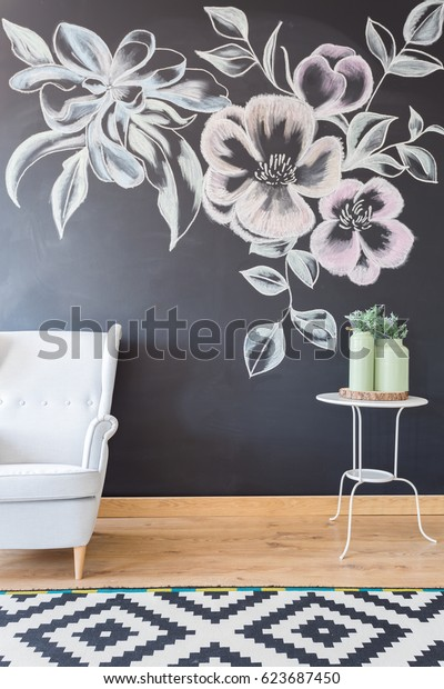 White comfortable armchair at blackboard wall with flowers