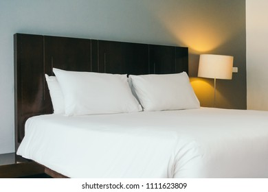 White comfortable pillow on bed decoration in hotel bed room