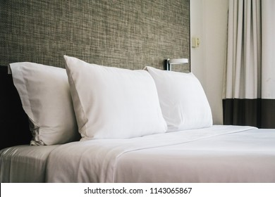 White comfortable pillow on bed decoration interior of hotel bedroom