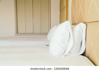 White comfortable pillow on bed decoration with light lamp in hotel bedroom interior