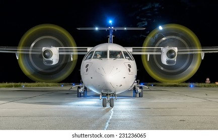 White commercial plane with engines running and propeller blur on a night with the moon on background