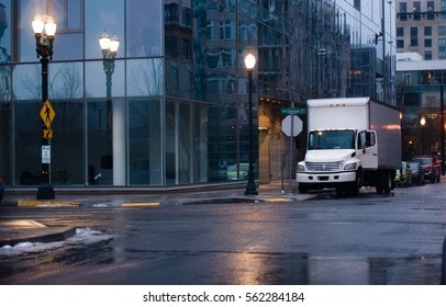 White compact small semi truck with a box trailer for local delivery of industrial goods and for moving residents of city stands on the evening rainy Portland street near modern multistorey building