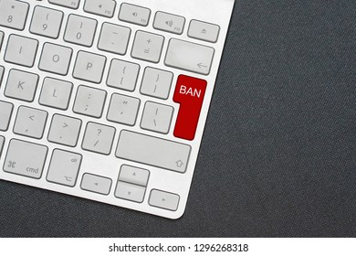 White computer keyboard and red key with word Ban. Black background.