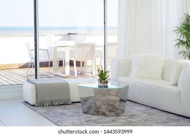 White Concept Living Room Interior. Modern bed room interior in Luxury villa. White colours, big window. Interior of the living room of the hotel. Beautiful living room with white sofa.