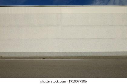 Weiße Betonwand mit horizontalen Blöcken. Gedeckter Bürgersteig und asphaltierte Straße vor dem Haus. Hintergrund für Kopienraum