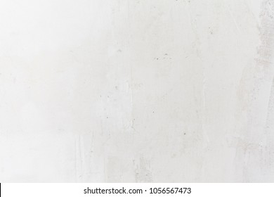 The white concrete wall. Small cracks on the surface