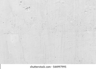 White concrete wall. Small cracks on the surface