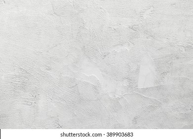 White concrete wall with stucco relief pattern, background photo texture