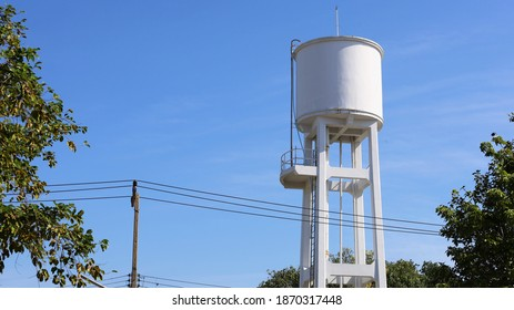 White concrete water tank on the tower. Large outdoor water tank for water supply in village or urban community. Beside there are green trees and bright sky background with copy area. Selective focus.
