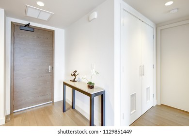 White condo entrance hall features console table atop light brown hardwood floor. Northwest, USA