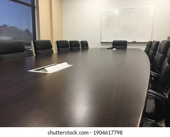 White conference room with a large brown table
