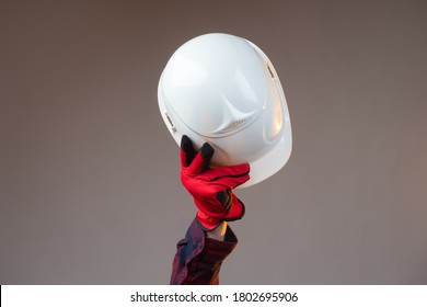 White construction helmet close-up. The man makes a greeting gesture with a white construction helmet. A gloved hand raises the helmet above his head.