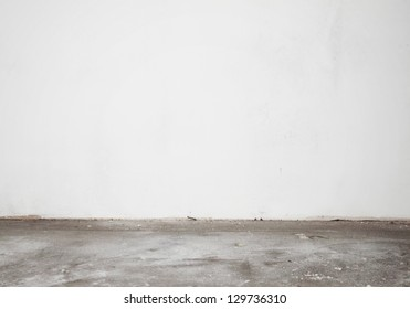 White construction stucco wall and cement floor