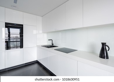 White contemporary kitchen with stone floor and black accessories