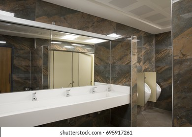 White Corian Sink, Chrome Tap, Wooden Doors and Dark Green Marble Textured Wall Tiles at Commercial Public Male Bathroom at Office Building