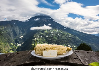 White corn with young cheese - typical food in the Andes. Plates with food on the background of the volcano Tungurahua, Banos de Agua Santa, Ecuador