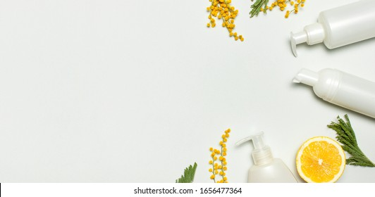 White cosmetic bottle containers with yellow Mimosa flowers and fresh lemon on gray background top view flat lay. Cosmetics SPA branding mock-up, Natural organic beauty product concept vitamin C