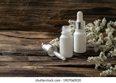 White cosmetic bottles and dropper with white small flowers  on wood background. Blank label for branding mock-up.