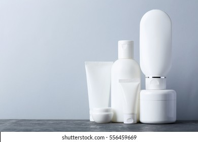 White cosmetic bottles on a grey table