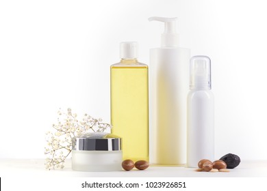 White cosmetic products with argan fruits for skin care and hair on a white background. Space for labels and graphics