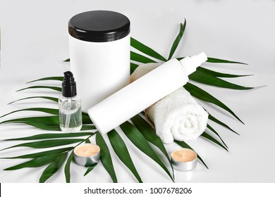 White cosmetic products and green leaf on white background. Natural beauty products for branding mock-up concept.