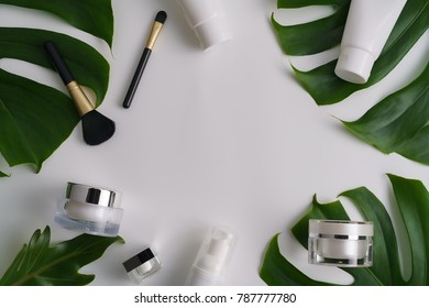White cosmetic products and green leaves on white background. Natural beauty blank label for branding mock-up concept.