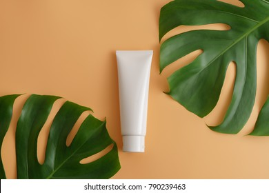 White cosmetic products and green leaves on color background. Natural beauty product for branding mock-up concept.