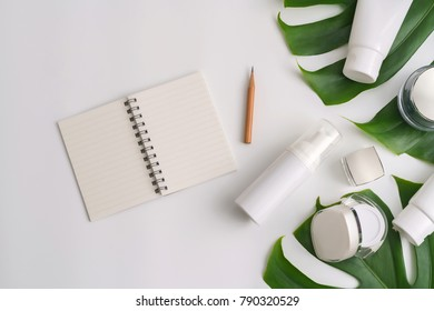 White cosmetic products and green leaves on white background. Natural beauty products for branding mock-up concept.