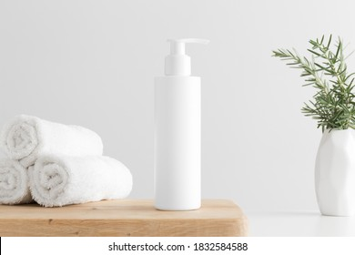 White cosmetic shampoo dispenser bottle mockup with towels and a rosemary  on a wooden table.