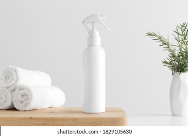 White cosmetic trigger sprayer bottle mockup with towels and a rosemary on a wooden table.