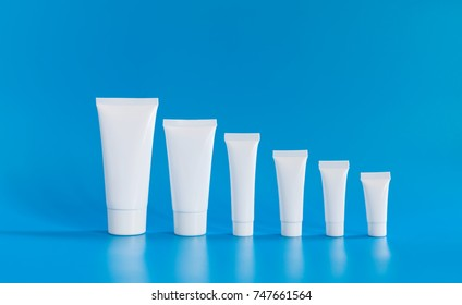 White cosmetic tube collection arranged small large on blue background. Abstract plastic containers different size capacity, blank template packaging design. copy space photo.
