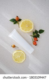 white cosmetic tube with lemon wedges and rose hips. Natural skin care concept.Copy space