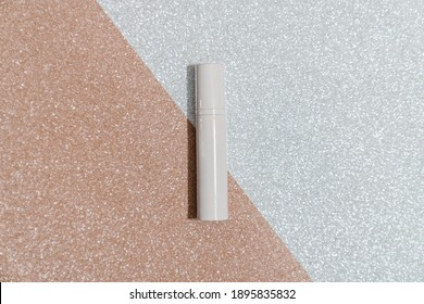 White cosmetic tube on gold and silver sparkling background. Flatlay, beauty ad concept, blog, minimalism, mockup, copyspace