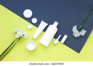White cosmetics concept on the yellow and grey background with  flowers. Summer beauty flat lay. Top view