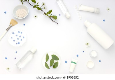White cosmetics flat lay frame with flowers and leaves. Clean beauty concept