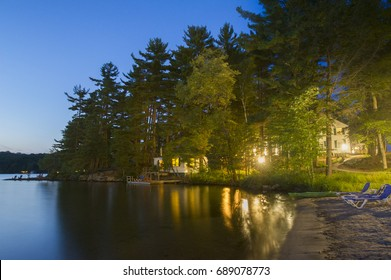 White cottage nested between green trees facing a calm lake at dusk. In the background are two Muskoka chairs. Long exposure capture