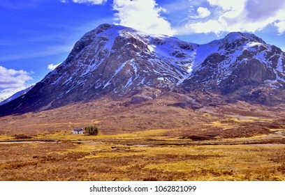 white cottage nestling below Glen Coe, mountain in the scottish Highlands. Argyle, Scotland UK. April 2018