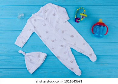 White cotton baby sleeper with head and toys. Kid woolen cardical, baby nipple, rattle and pacifier, top view.