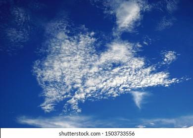 White cotton ball texture clouds against dark royal blue sky