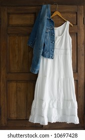 White cotton dress and jeans jacket on wooden hanger on antique wardrobe