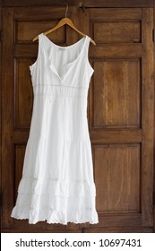 White cotton dress on wooden hanger on antique wardrobe
