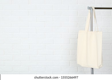 White cotton eco bag hanging on clothes rack