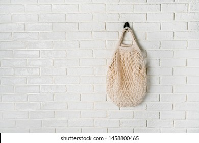 White cotton net bag hanging on whitewall. High resolution