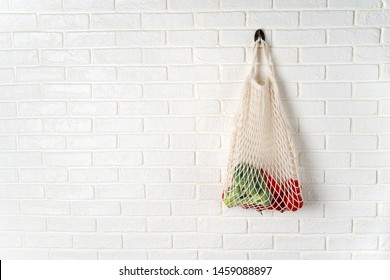White cotton net bag with vegetables hanging on whitewall. High resolution